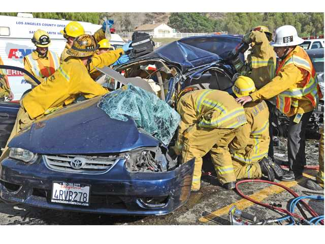 L.A. County firefighters use the Jaws of Life to extricate the occupant of a Toyota four-door sedan that collided with a Mitsubishi sedan on San Francisquito Canyon Road about 2.5 miles north of Copper Hill Drive on Wednesday. Signal photo by Dan Watson