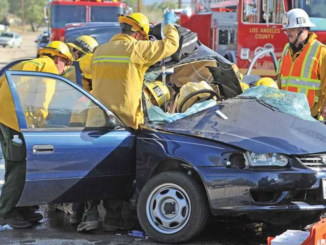Firefighters have an intravenous line in place on the occupant of a Toyota sedan that collided with a Mitsubishi sedan on San Francisquito Canyon Road on Wednesday about 2.5 miles north of Copper Hill Drive. Signal photo by Dan Watson