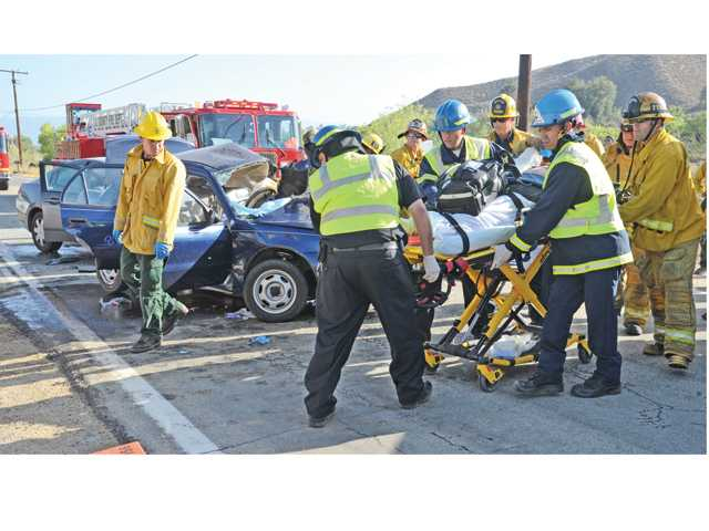 L.A. County firefighters extricate the occupant of a Toyota sedan after it was involved in a collision with a Mitsubishi sedan Wednesday about 2.5 miles north of Copper Hill Drive on San Francisquito Canyon Road. Signal photo by Dan Watson