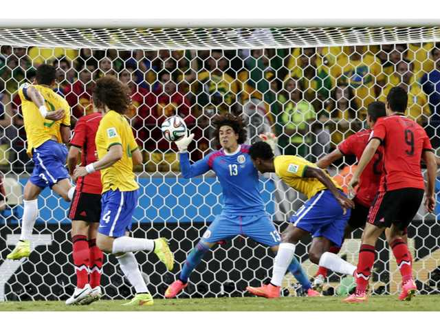 Mexico's goalkeeper Guillermo Ochoa (13) bats the ball away after a header by Brazil's Fred, left, during a World Cup match in Fortaleza, Brazil on Tuesday.