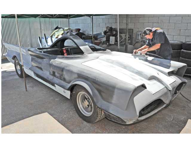 Car restorer Ernie Lepore sands the fiberglass fender as he works on his batmobile replica at German Autohaus auto repair in Newhall on Wednesday. Signal photo by Dan Watson.