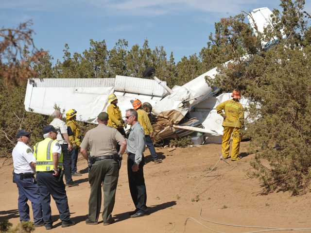 Sheriff's Department investigators and L.A. County Fire Department officials examine a light plane that crashed Friday near Shady Lane Road and Sierra Highway in Agua Dulce. Signal photo by Dan Watson