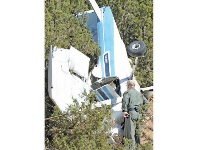 A man examines a light plane that crashed in Agua Dulce on Friday. Two people were seriously injured and taken to Henry Mayo Newhall Hospital. Signal photo by Dan Watson.