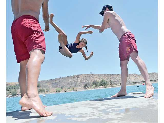 Claire Miller, 9, gets her turn to be tossed in the lake by instructors Tyler Miller, left, and Alex Anthony at Castaic Lake's Junior Lifeguard's Program during the first session. Signal photo by Katharine Lotze.