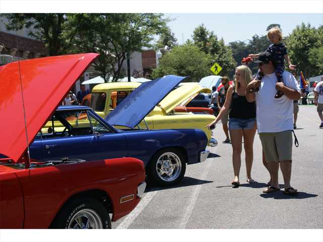 Danielle Bustos, left, takes in the fifth annual Old Town Newhall Classic Car Show Sunday with her husband, Chris, and their 3-year-old son, Ayden, on his shoulders. Signal photo by Jim Holt.