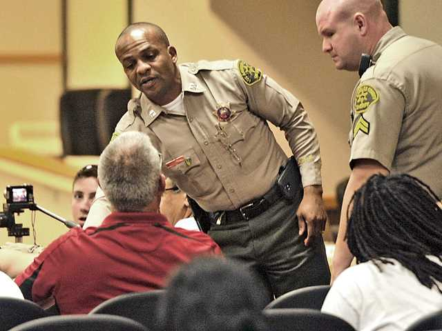 Sheriff's Capt. Roosevelt Johnson, left standing, reaches to escort Saugus resident Steve Petzold, seated, from Council Chambers during the sometimes-contentious Santa Clarita City Council meeting Tuesday night at which members agreed to put the billboard ordinance to a public vote. Signal photo by Katharine Lotze