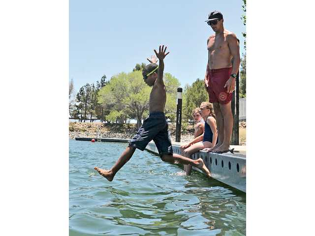 Junior lifeguards in the 9 to 11-year-old age group push their instructor, Alex Anthony off the dock at the Castaic Lake Junior Lifeguard Program on June 18.