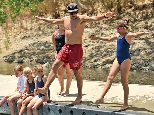 Kyra Muinos, 11, gets instruction on how to safely enter the water from the dock from instructor Alex Anthony at the Castaic Lake Junior Lifeguard Program on June 18.