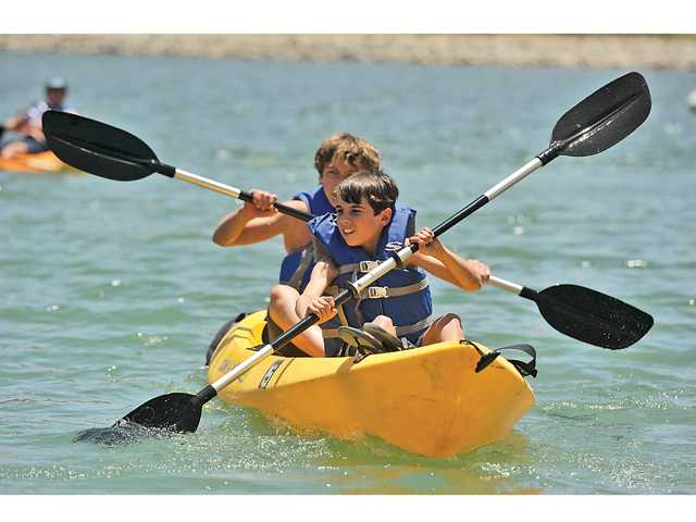 Two junior lifeguards paddle their kayak out onto Castaic Lagoon at the Castaic Lake Junior Lifeguard Program on June 18.