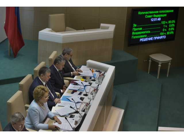 Speaker of Federation Council members Valentina Matviyenko, second left, looks at the screen in front of her during the voting in the Russian parliament's upper chamber.