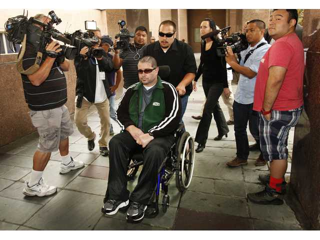 A wheelchair bound Bryan Stow, is surrounded by family and media as he is led into the Los Angeles County Superior Courthouse in downtown Los Angeles, Wednesday, June 25.