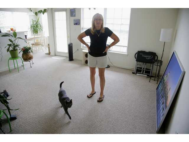 Julie Pemberton stands in the living room of her apartment as her cat Pewter walks through, Thursday, June 26, 2014.