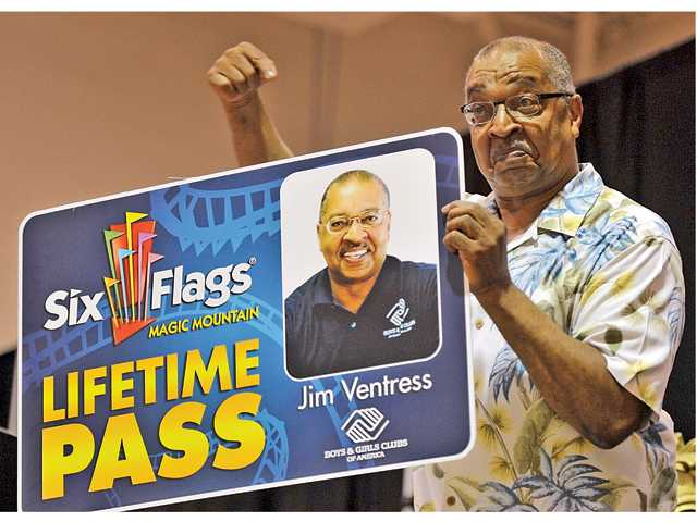 Jim Ventress shows off his new lifetime pass to Six Flags Magic Mountain to attendees of his retirement party.