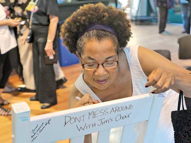 Judi Ventress signs a rocking chair for her brother Jim Ventress,