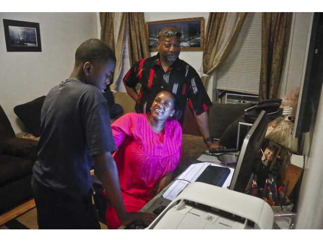 In this June 17, 2014 photo, Melissa Carter, center, chats with her son William, 13, before joining her fiance Addullah Salahuddin, right, at the computer to prepare they wedding music playlist in New York