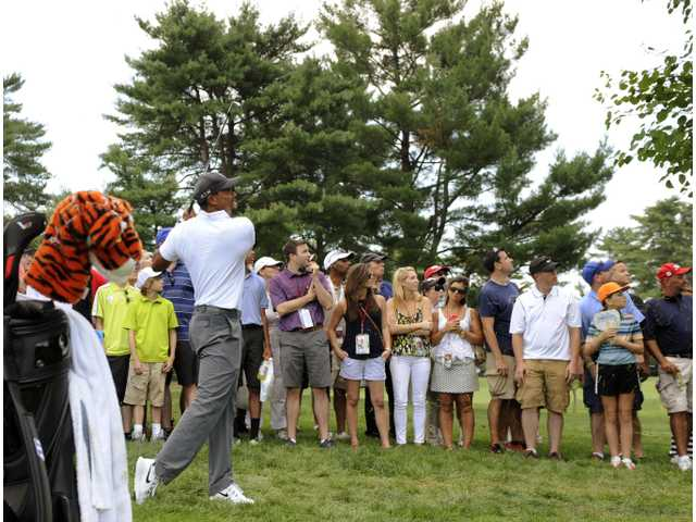 Tiger Woods hits from the rough on the ninth hole during the second round of the Quicken Loans National golf tournament Friday in Bethesda, Md.