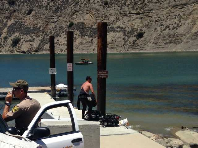 A sheriff's deputy, left, speaks to searchers from a sheriff's cruiser as a diver, right, stands near the victim's covered body at Pyramid Lake on Sunday.