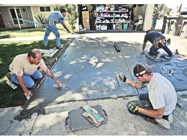 Volunteers from the City of Santa Clarita Public Works department help install the cement driveway at a house used for Family Promise SCV Resource Center in Canyon Country on Saturday.