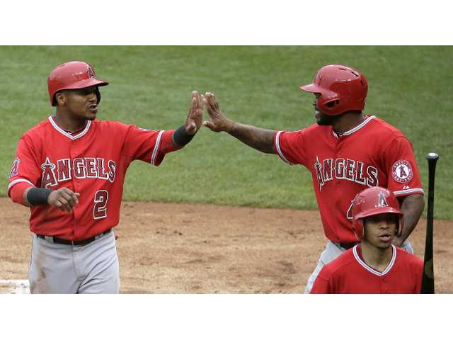 Los Angeles Angels' Erick Aybar (2) and Howie Kendrick (47) celebrate after they scored on a single by David Freese during the sixth inning of Saturday's game in Kansas City, Mo.