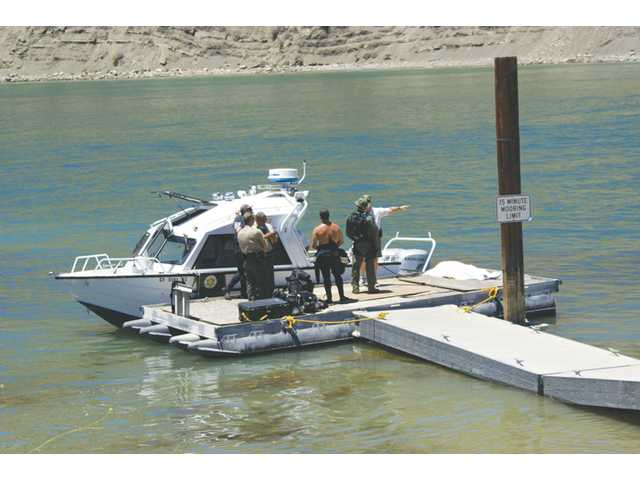 Search crews gather on a dock at Pyramid Lake Sunday as a Sheriff's Department Parks Bureau patrol boat returns from a search near where the victim's body, right, covered, was found. Signal photo by Jim Holt.