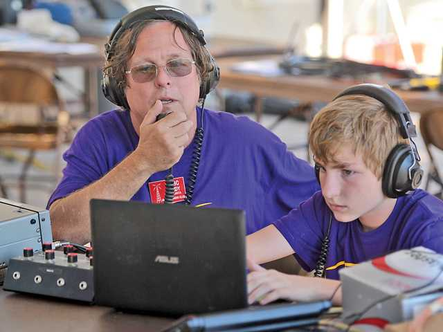 Randy Comeau and his son, Sean, attempt to contact other amateur radio operators during the Santa Clarita Amateur Radio Club's participation in the Amateur Radio Field Day, an international competition for amateur radio operators, at Castaic Lake Water Agency in Saugus on Saturday. Signal photo by Katharine Lotze.
