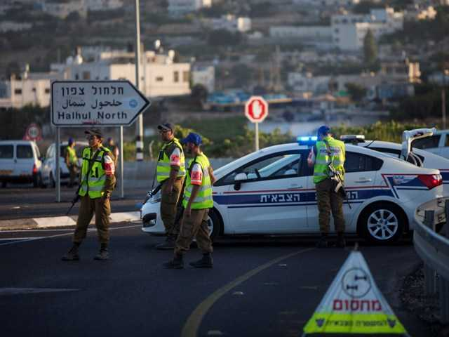 Israeli police officers block a road in the village of Halhul where the bodies of three missing Israeli teenagers were found Monday