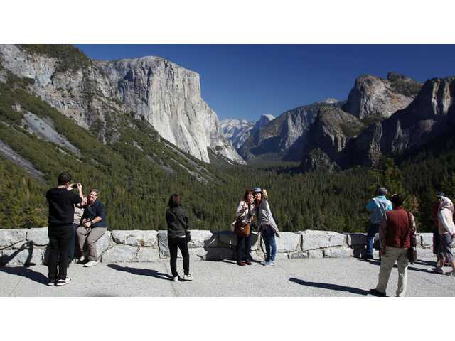 In this Oct. 17, 2013 file photo, visitors at Tunnel View, like Kaori Nishimura and Eriko Kuboi, from Japan, center facing, enjoy the views of Yosemite National Park, Calif. Tunnel View is a scenic vista which shows off El Capitan, Half Dome and Bridalveil Fall. Yosemite National Park is celebrating the 150th anniversary of President Abraham Lincoln's signing of the Yosemite Grant Act, Monday June 30, 2014, which protected Yosemite Valley and Mariposa Grove. (AP Photo/Gary Kazanjian, File)
