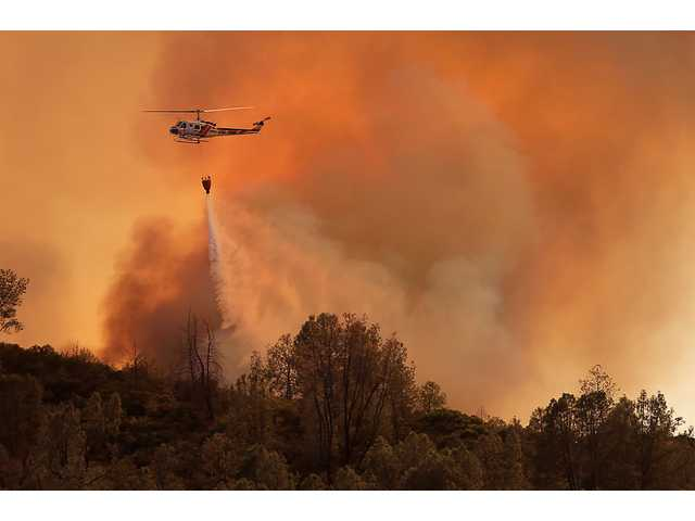 A Cal Fire helicopter makes a drop on the Butts Canyon Fire on Tuesday, July 1, 2014, near Middletown, Calif.