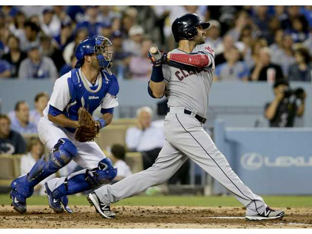 Cleveland Indians' Nick Swisher, right, watches his two-RBI double as Los Angeles Dodgers catcher Drew Butera looks on in Los Angeles on Tuesday.