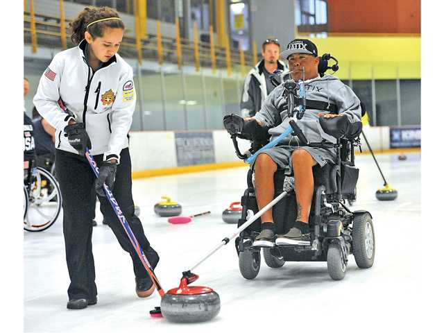 Andie McDonald helps keep the curling stone in a straight line for Russel Burke as he prepares to release it during the Triumph Foundation and Hollywood Curling's wheelchair curling clinic at Ice Station Valencia on June 28. Signal photo by Katharine Lotze