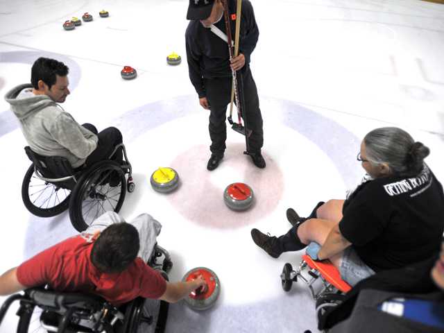 "Wheelchair curling clinic attendees tally up the score of their game at Ice Station Valencia. The winner of a match is determined by the closest stone to the center of the ""house,"" which resembles a target. Signal photo by Katharine Lotze"