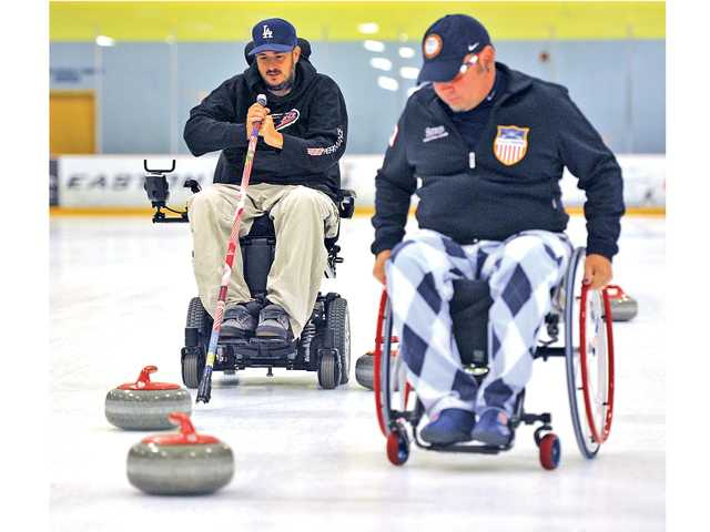 Frank Alito throws a stone as instructor and two-time U.S. paralympian curler Patrick McDonald instructs him on how to keep the stone in a straight line during the Triumph Foundation and Hollywood Curling's wheelchair curling clinic at Ice Station Valencia on June 28. Signal photo by Katharine Lotze
