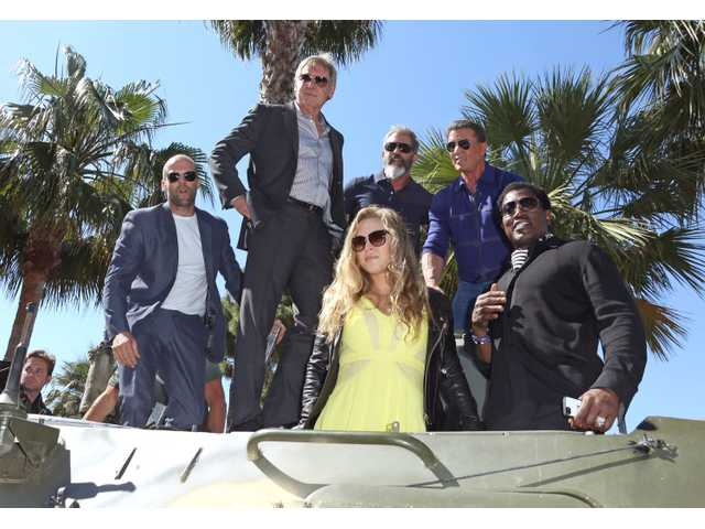 In this May 18, 2014 file photo, from left, Jason Statham, Harrison Ford, Mel Gibson, Sylvester Stallone, Wesley Snipes and Ronda Rousey ride a tank during a photo call for The Expendables 3.
