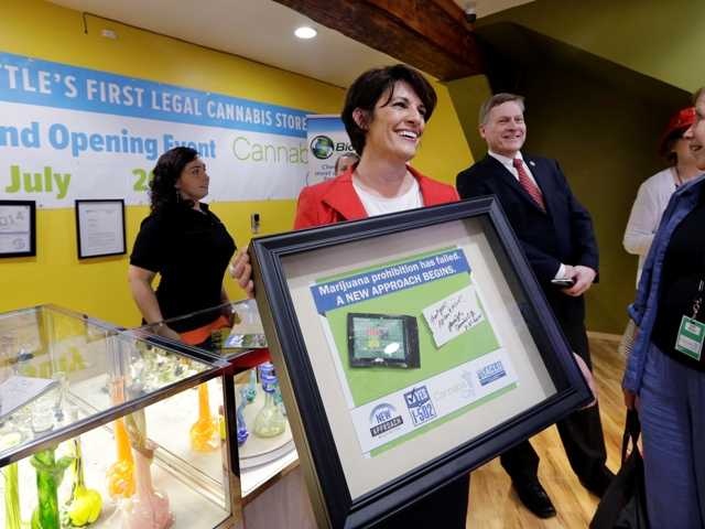 Alison Holcomb, left, criminal justice director at the Washington state ACLU, holds her framed first-purchase of legal marijuana