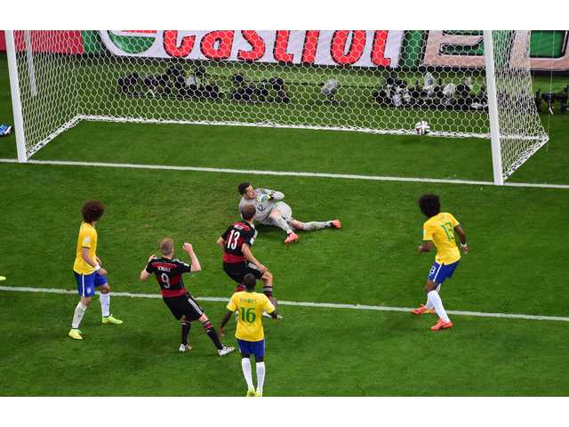 Germany's Andre Schuerrle, second left, scores his side's 6th goal during the World Cup semifinal soccer match between Brazil and Germany at the Mineirao Stadium in Belo Horizonte, Brazil on Tuesday.