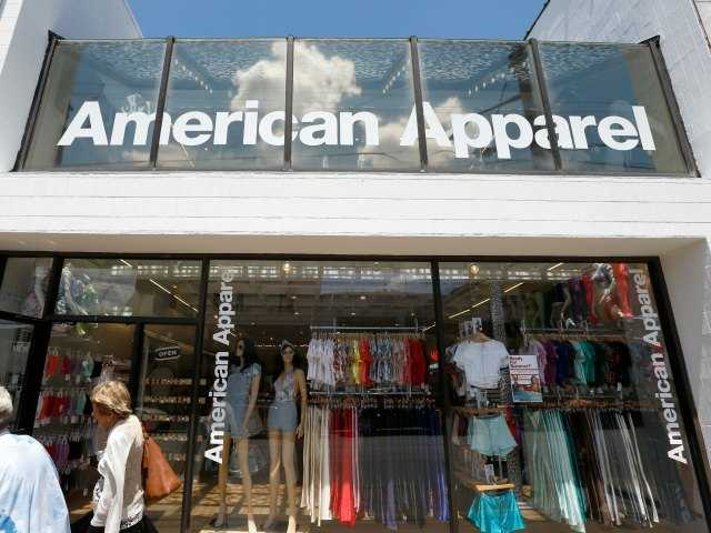 Passers-by walk down the street past the American Apparel store in the Shadyside neighborhood of Pittsburgh on Wednesday, July 9, 2014. (AP Photo/Keith Srakocic)