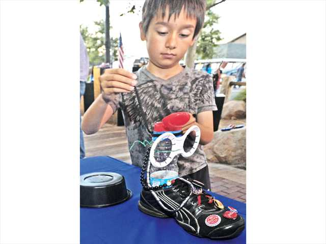 "Wesley Hamshaw, 10, adds pieces as he decorates a shoe as part of the Art Tree's Great American Shoe Project shoe gallery at the Art Slam ""A Celebration of Patriotic Art"" event held on Main Street in Newhall on Thursday.  Signal photo by Dan Watson."