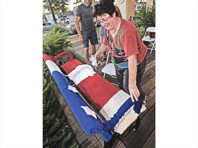 "Julie Kornblum adds stars to the bench she has decorated with yarn in patriotic colors in a ""yarn bomb"" at Art Slam ""A Celebration of Patriotic Art"" held on Main Street in Newhall on Thursday. Signal photo by Dan Watson."