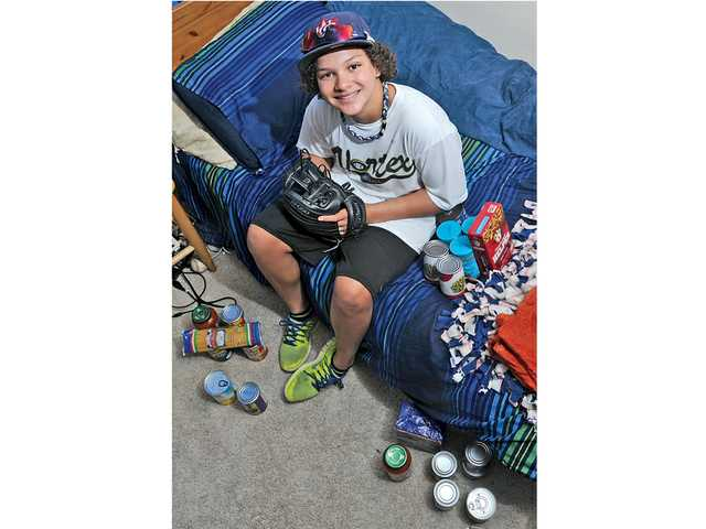 "Hunter Ventress, 13, poses in his bedroom with his new glove and the food he's gathered so far for his ""pay it forward"" food drive inspired by the kindness of strangers. Signal photo by Katharine Lotze"
