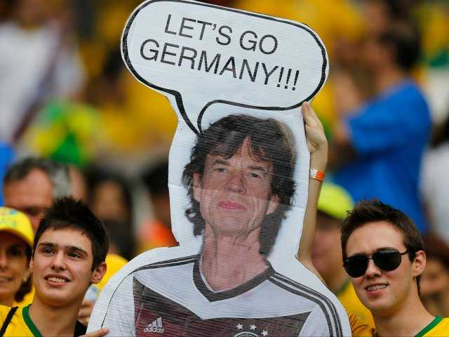 Brazil supporters hold a poster depicting Rolling Stones singer Mick Jagger wearing a Germany shirt prior to the World Cup semifinal soccer match between Brazil and Germany at the Mineirao Stadium in Belo Horizonte, Brazil, Tuesday, July 8, 2014. (AP Photo/Frank Augstein)