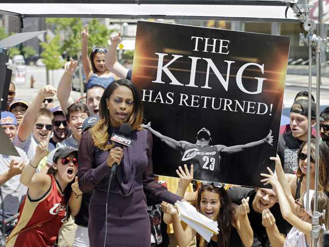 Fans whoop it up behind an ESPN reporter outside Quicken Loans Arena in Cleveland after NBA basketball star LeBron James announced he would return to the Cleveland Cavaliers on Friday.