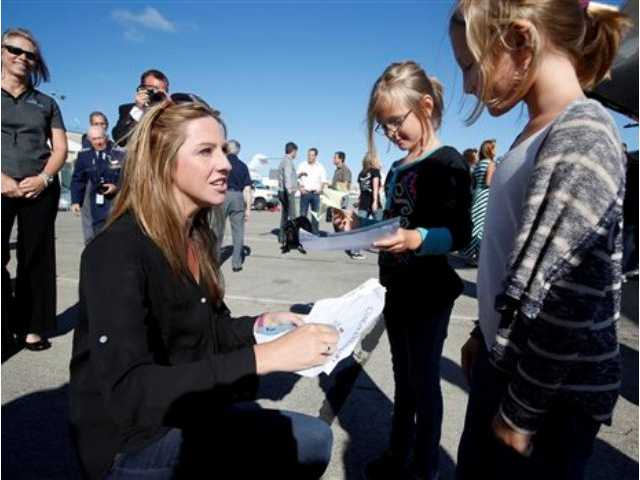 Amelia Rose Earhart, left, is greeted by twins Addison, and Natalie Boland, 7, right, of Thousand Oaks, Calif., after arriving at North Field in Oakland, Calif., on Friday, July 11, 2014.