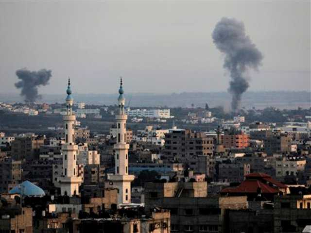 Columns of smoke rise following Israeli strikes on Gaza Strip, Saturday, July 12, 2014. Israeli airstrikes on Gaza hit a mosque and a center for the disabled where a few women were killed Saturday.