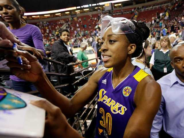 Los Angeles Sparks' Nneka Ogwumike stops to sign autographs as she leaves the court after a WNBA basketball game against the Seattle Storm Thursday, July 3, 2014, in Seattle. Ogwumike led all scorers with 21 points and the Sparks won 70-56. (AP Photo/Elaine Thompson)