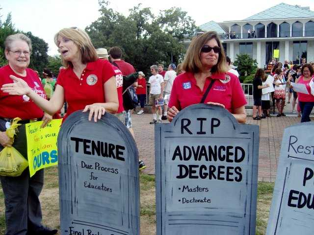 People gather outside the North Carolina General Assembly in Raleigh, NC during summer 2013 to protest the elimination of tenure and extra pay for teachers with advanced degrees in the state. Efforts to eliminate extra pay for teachers who earn advanced degrees are gaining momentum in a small but growing number of U.S. schools. Among issues related to teacher pay that legislators are debating this summer include reinstating the extra pay for those teaching in the subject in which they got their advanced degree. (AP Photo/NCPolicyWatch.com)