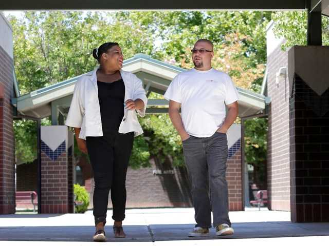 Elk Grove Unified School District teacher Michael Jones and former student Kandance Stagner, a foster child, walk around Laguna Creek High School Friday