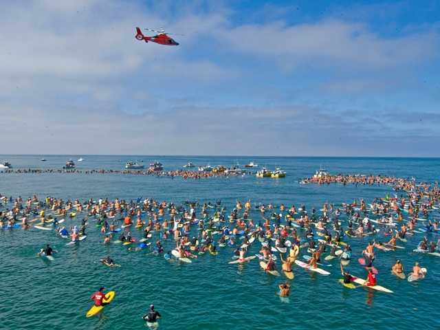A Coast Guard helicopter hovers over people gathered for a memorial for Newport Beach lifeguard, Ben Carlson