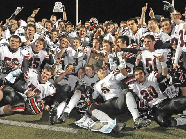 The Hart football team celebrates winning the CIF-Southern Section Northern Division championship.