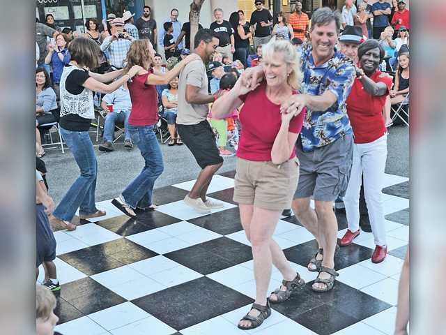 "Dancers form a conga line on the dancefloor at the Senses ""Rockabilly"" concert on Main Street in downtown Newhall Thursday evening. Signal photo by Katharine Lotze."