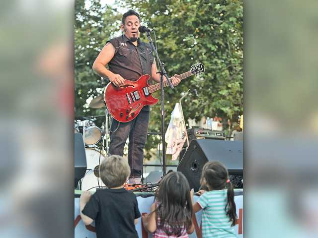 The lead vocalist and guitarist for the Hard Six, who goes by Fuse, talks with a few young fans at Thursday night's Senses event on Main Street in downtown Newhall. Signal photo by Katharine Lotze.